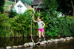 Cute little girl crossing river with cane Stock Photo