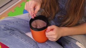 Cute little girl with cup of hot cocoa drink. Close up stock footage