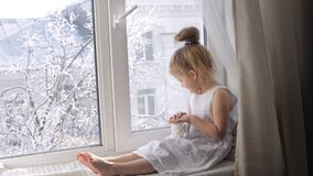 Cute little girl with a cup of tea sitting on window sill. Girl with cup looking through the window. Sunny winter stock video
