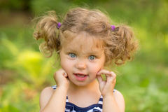 Cute little girl with curly blond hair. And blue eyes outdoors Stock Image