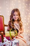 Cute little girl with curly hair with a gift on Christmas Eve, before the New Year. Cheerful emotions in anticipation of a surprise stock photos