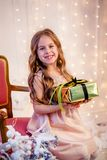 Cute little girl with curly hair with a gift on Christmas Eve, before the New Year. Cheerful emotions in anticipation of a surprise royalty free stock image