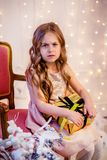 Cute little girl with curly hair with a gift on Christmas Eve, before the New Year. Sad emotions in anticipation of a surprise stock images