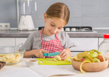 Cute little girl cutting apples for strudel Royalty Free Stock Photography