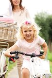 Cute little girl cycling in park with mother in background. Portrait of cute little girl cycling in park with mother in background stock photos