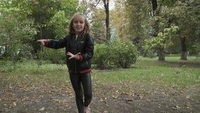 Cute little girl dances in slowmotion in park stock footage