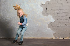 Cute little girl dancing, jumping, smiling and posing to camera. Cute toddler girl jumping joyfully. Dancing and laughing. Vintage background. Happy childhood Royalty Free Stock Photos