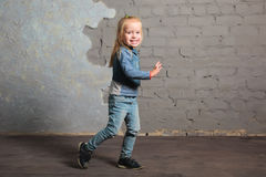 Cute little girl dancing, jumping, smiling and posing to camera. Cute toddler girl posing joyfully to camera. Dancing, jumping, running, laughing. Happy Stock Photo