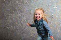 Cute little girl dancing, jumping, smiling and posing to camera. Cute toddler girl posing joyfully to camera. Dancing, jumping, running, laughing. Vintage Stock Image