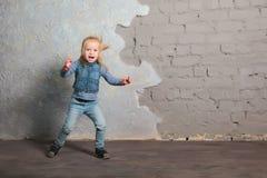 Cute little girl dancing, jumping, smiling and posing to camera. Cute toddler girl posing joyfully to camera. Dancing, jumping, running, laughing. Vintage Stock Photos