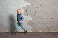 Cute little girl dancing, jumping, smiling and posing to camera Royalty Free Stock Image