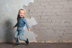 Cute little girl dancing, jumping, smiling and posing to camera. Cute toddler girl posing joyfully to camera. Dancing, jumping, running, laughing. Vintage Stock Photo