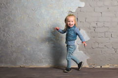 Cute little girl dancing, jumping, smiling and posing to camera Stock Image