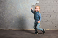 Cute little girl dancing, jumping, smiling and posing to camera. Cute toddler girl posing joyfully to camera. Waving hand and laughing. Vintage background. Happy Royalty Free Stock Images