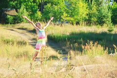Beautiful little girl Is dancing in the meadow at summer sunset Royalty Free Stock Image