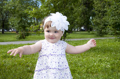 Cute little girl dancing in the park. Background green grass and trees Stock Photos