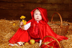 Cute little girl with dandelions wearing in red clothing resting Royalty Free Stock Images