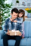 Cute little girl, daughter, sister hugs father or brother and gives him a gift.  stock photos