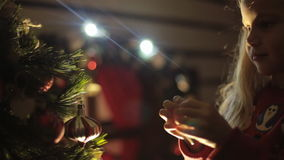 Cute little girl decorates Christmas tree for the stock video footage