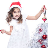 Cute little girl is decorating christmas tree Royalty Free Stock Image