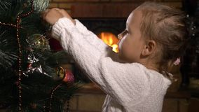 Cute little girl decorating Christmas tree in dark room with fireplace stock video footage