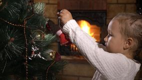 Cute little girl decorating Christmas tree in dark room with fireplace stock video