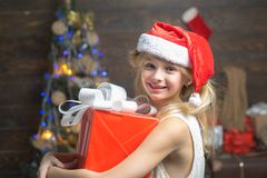Cute little girl is decorating the Christmas tree indoors. Happy children. Happy small teenager in Santa hat with stock photography