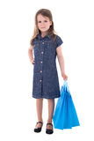 Cute little girl in denim dress with shopping bags isolated on w Royalty Free Stock Photos