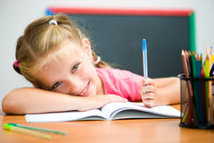 Cute little girl at the desk Royalty Free Stock Images