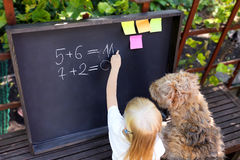 Cute little girl  with dog writing answer to the exercise using chalk on blackboard Royalty Free Stock Photos