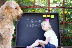 Cute little girl  with dog writing answer to the exerciseusing chalk on blackboard Royalty Free Stock Image