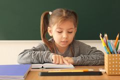Cute little girl doing homework. In classroom Stock Photos