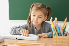Cute little girl doing homework. In classroom Stock Photography