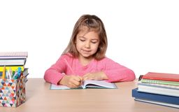 Cute little girl doing homework. Against white background Stock Photography