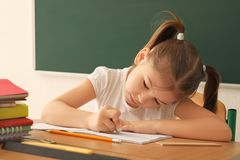 Cute little girl doing homework. In classroom Stock Image