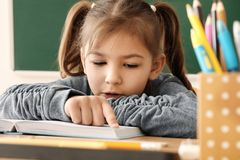 Cute little girl doing homework. In classroom Stock Photo