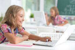Cute little girl doing homework. With laptop at home Stock Photography