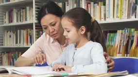 Cute little girl doing homework with her mother. Beautiful mature Asian woman helping her adorable little daughter with homework studying at the library stock footage