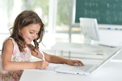Cute little girl doing homework. With laptop at home Royalty Free Stock Photos