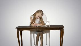 Cute little girl doing homework, writing down on white background. Professional shot in 4K resolution. 095. You can use it e.g. in your commercial video royalty free stock photo