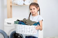 Cute little girl doing laundry. At home stock photo