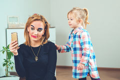 Cute little girl are doing makeup and hairstyle for her beautiful mother. Toned. Royalty Free Stock Images