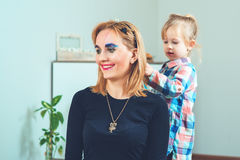Cute little girl are doing makeup and hairstyle for her beautiful mother. Toned. Royalty Free Stock Image