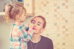 Cute little girl are doing makeup for her beautiful mother. Toned. Royalty Free Stock Photos