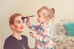 Cute little girl are doing makeup for her beautiful mother. Toned. Stock Photo