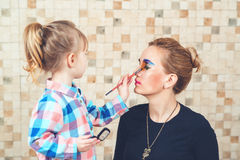 Cute little girl are doing makeup for her beautiful mother. Toned. Stock Photos