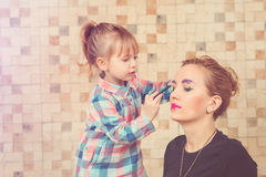 Cute little girl are doing makeup for her beautiful mother. Toned. Stock Photography