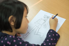 Cute little girl is drawing Cartoon Stock Image