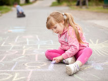 Cute little girl drawing with chalk outdoors Stock Photos