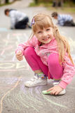 Cute little girl drawing with chalk outdoors Stock Photo